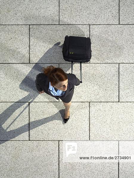 Eine Geschäftsfrau  die einen Koffer zieht.