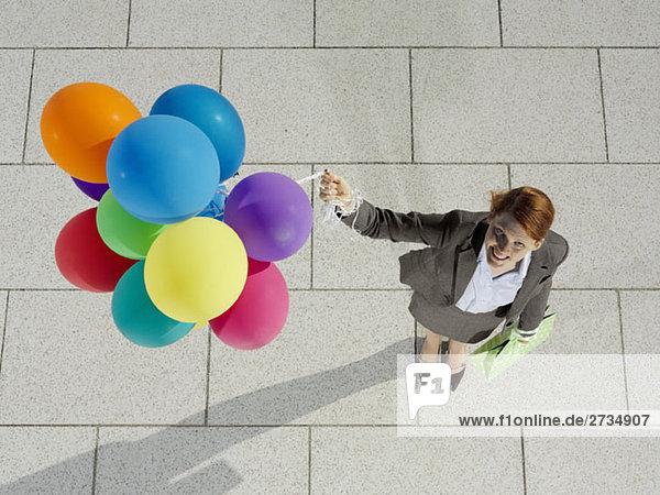 Eine junge Frau mit einem Haufen Luftballons