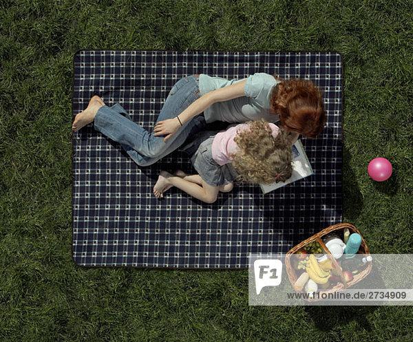 Mutter und Tochter liegen auf einer Decke im Gras und lesen ein Buch.