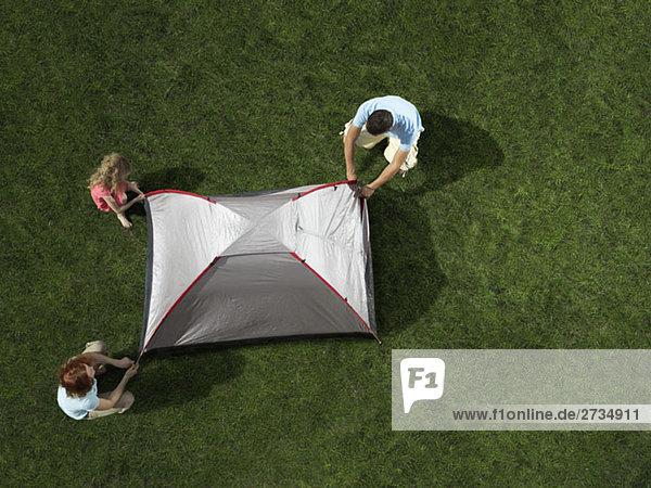 Eine junge Familie baut ein Zelt auf.