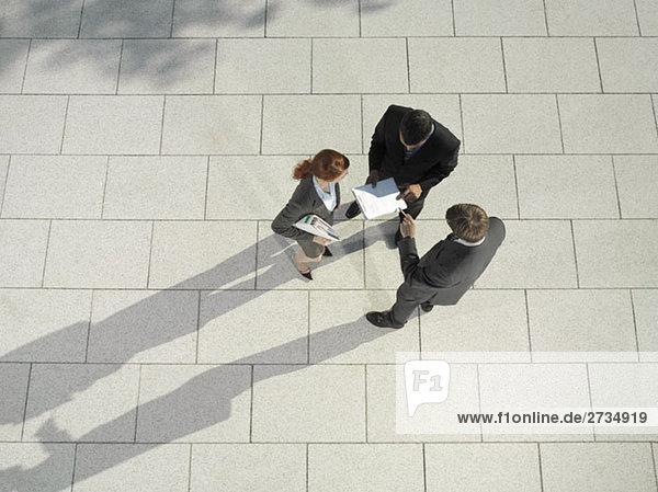 Drei Geschäftsleute  die draußen stehen und diskutieren.