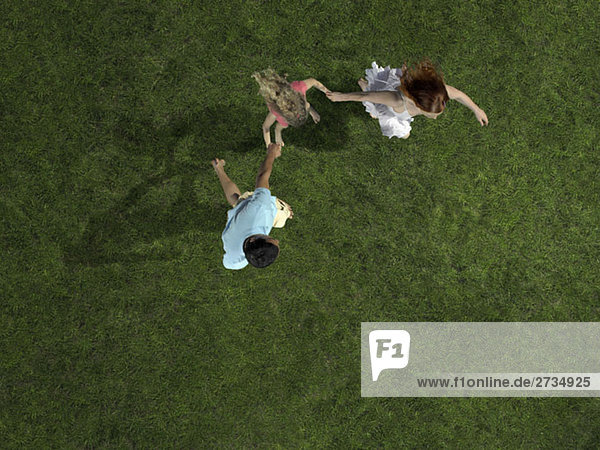 Eine junge Familie hält sich an den Händen und rennt auf Gras.