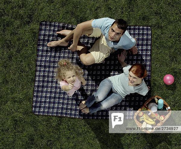 Eine Familie  die auf einer Decke sitzt und ein Picknick macht.