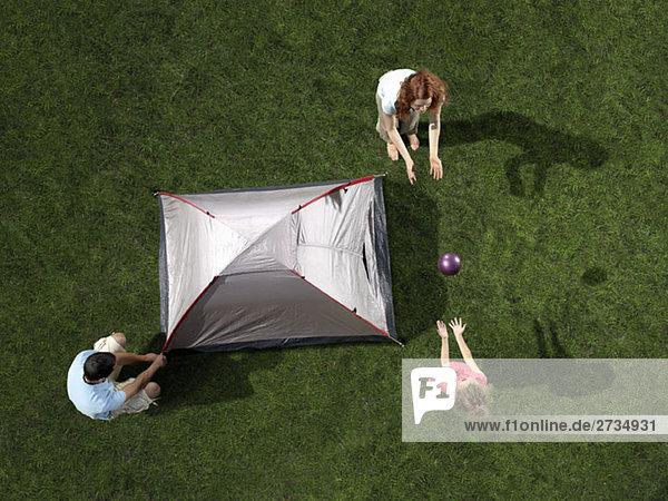 Eine junge Familie baut ein Zelt auf und spielt mit einem Ball.