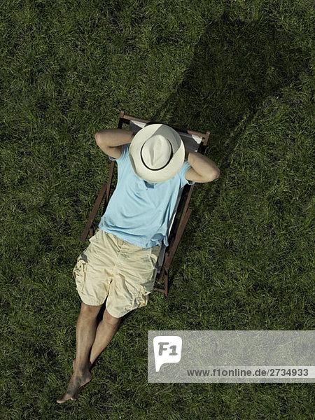 Ein Mann  der auf einer Sonnenliege sitzt.