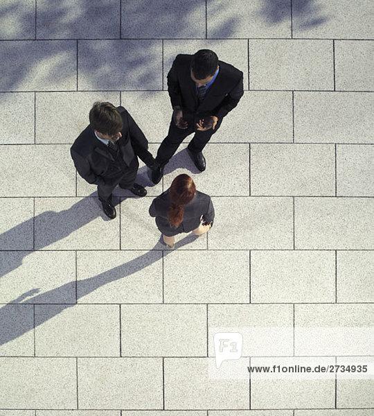 Drei Geschäftsleute sprechen im Freien