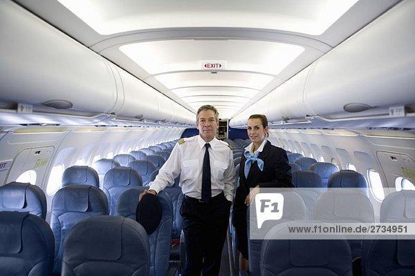 Ein Pilot und eine Flugbegleiterin stehen in der Kabine eines Flugzeugs. Ein Pilot und eine Flugbegleiterin stehen in der Kabine eines Flugzeugs.