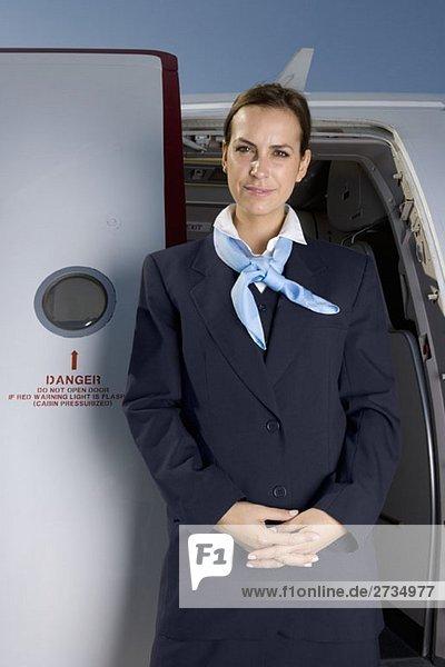 Eine Flugbegleiterin  die vor einer Flugzeugtür steht. Eine Flugbegleiterin, die vor einer Flugzeugtür steht.