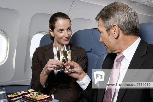 Ein Geschäftsmann und eine Geschäftsfrau rösten Champagnergläser im Flugzeug.