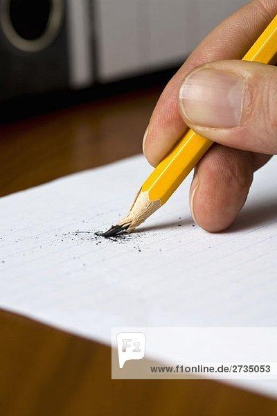 Eine Hand hält einen Bleistift  wenn die Spitze bricht.