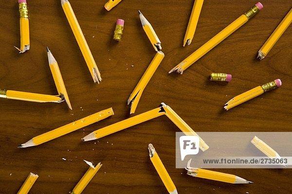 Ein Schreibtisch mit zerbrochenen Bleistiften.