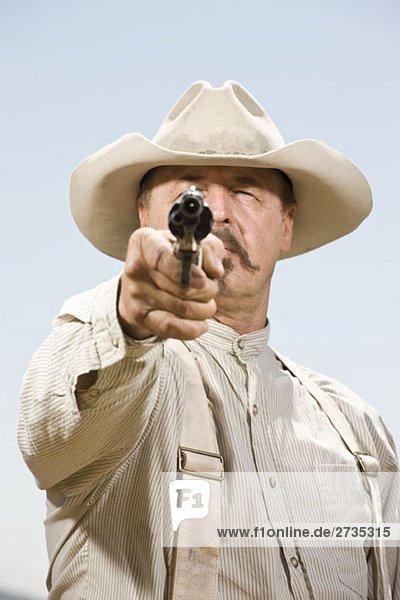 Porträt eines Cowboys mit schussbereiter Waffe Porträt eines Cowboys mit schussbereiter Waffe