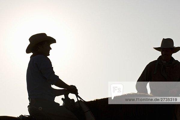 Silhouette zweier Cowboys auf Pferden sitzend Silhouette zweier Cowboys auf Pferden sitzend