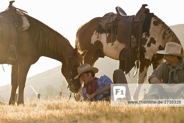 Zwei Cowboys  die sich mit ihren Pferden ausruhen. Zwei Cowboys, die sich mit ihren Pferden ausruhen.