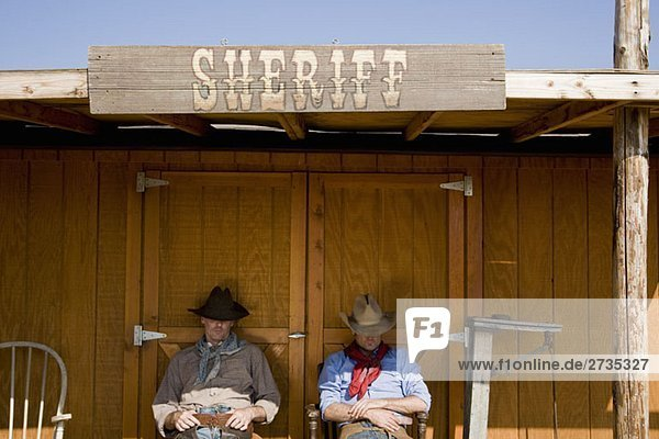 Zwei Cowboys sitzen vor dem Büro des Sheriffs. Zwei Cowboys sitzen vor dem Büro des Sheriffs.