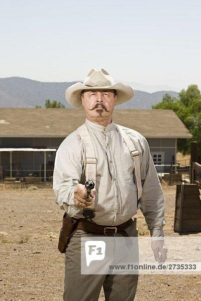 Porträt eines Cowboys  der auf seine Waffe zielt. Porträt eines Cowboys, der auf seine Waffe zielt.