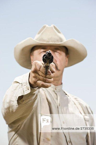 Nahaufnahme eines Cowboys  der auf seine Waffe zielt. Nahaufnahme eines Cowboys, der auf seine Waffe zielt.