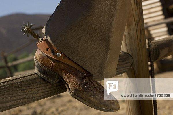 Der Lederstiefel eines Cowboys  der auf einem Zaun ruht. Der Lederstiefel eines Cowboys, der auf einem Zaun ruht.