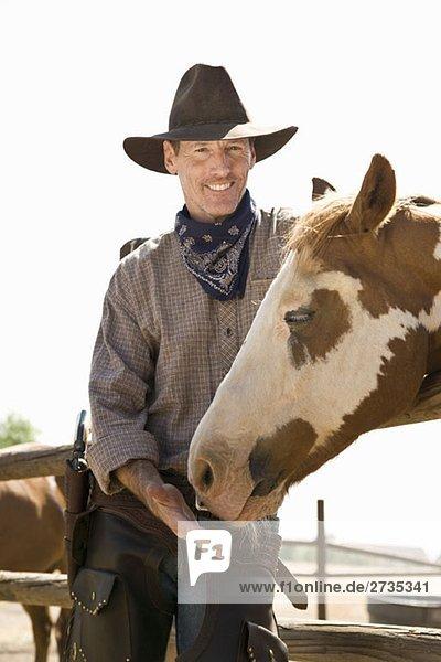 Ein Rancher stehend mit seinem Pferd Ein Rancher stehend mit seinem Pferd