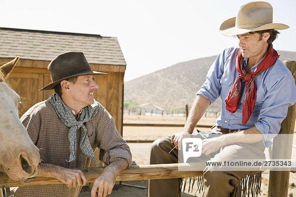 Zwei Rancher  die sich an einem Zaun ausruhen. Zwei Rancher, die sich an einem Zaun ausruhen.
