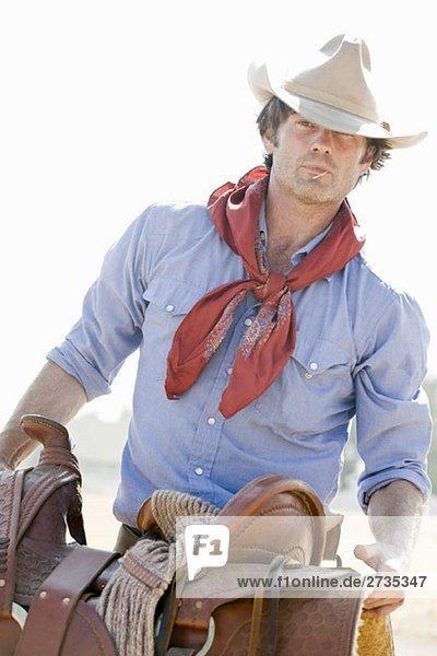 Ein Cowboy mit einem Pferdesattel Ein Cowboy mit einem Pferdesattel