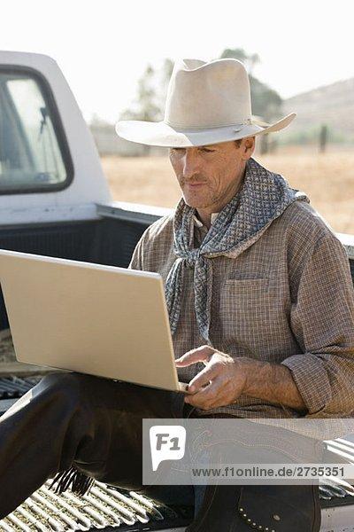 Ein Cowboy sitzt auf dem Rücken auf einem LKW und benutzt seinen Laptop. Ein Cowboy sitzt auf dem Rücken auf einem LKW und benutzt seinen Laptop.