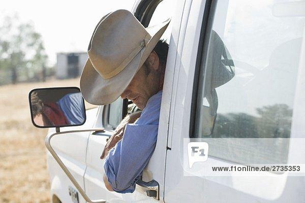 Ein Mann  der sich aus seinem Truck lehnt und nach unten schaut. Ein Mann, der sich aus seinem Truck lehnt und nach unten schaut.