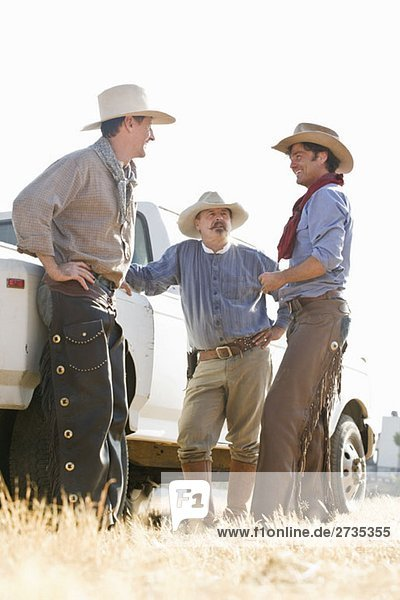 Drei Cowboys stehen auf einem Feld neben einem Lastwagen. Drei Cowboys stehen auf einem Feld neben einem Lastwagen.