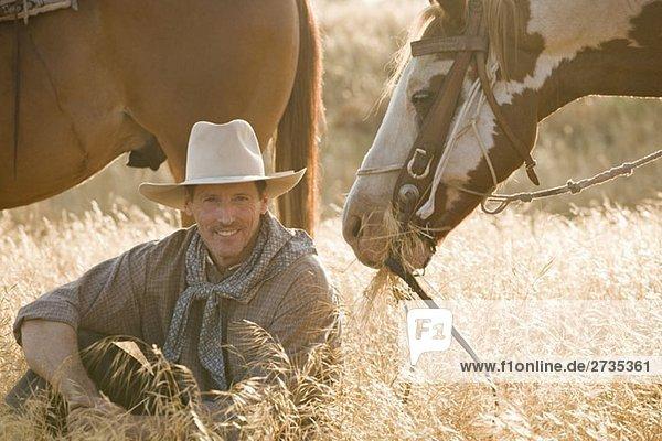 Ein Cowboy sitzt im langen Gras mit zwei Pferden. Ein Cowboy sitzt im langen Gras mit zwei Pferden.