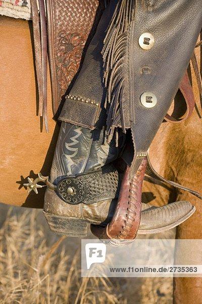 Das Bein eines Cowboys im Pferdesteigbügel Das Bein eines Cowboys im Pferdesteigbügel