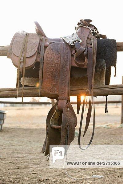 Ein an einem Zaun hängender Sattel Ein an einem Zaun hängender Sattel
