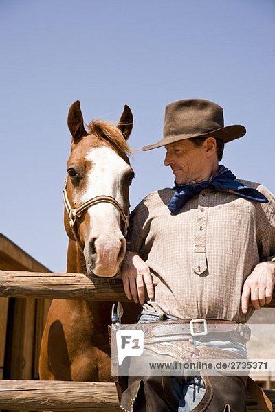 Porträt eines Cowboys  der neben einem Pferd steht Porträt eines Cowboys, der neben einem Pferd steht
