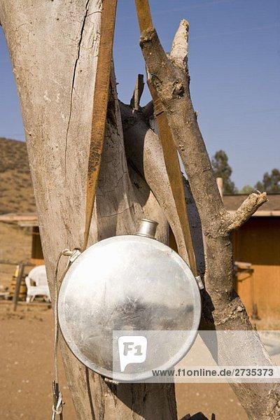 Ein Wasserbehälter aus Metall  der an einem Baum hängt. Ein Wasserbehälter aus Metall, der an einem Baum hängt.
