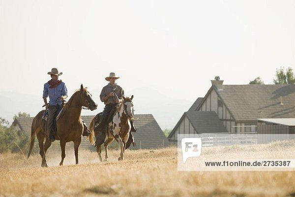Zwei Cowboys reiten Pferde durch ein Feld. Zwei Cowboys reiten Pferde durch ein Feld.