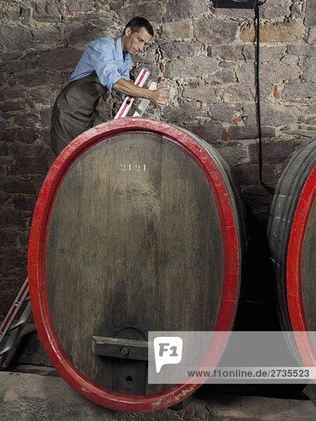 Ein Winzer  der einen Glaswein-Dieb benutzt  um eine Probe von einem Fass zu bekommen.
