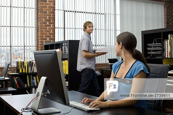 A woman typing and looking at a colleague