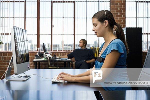 Eine Frau  die ein Headset trägt und einen Computer in einem Büro benutzt.