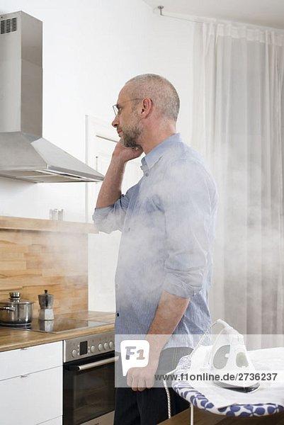 Ein Mann telefoniert mit dem Rücken zu einem Bügeleisen  das sein Hemd verbrennt.