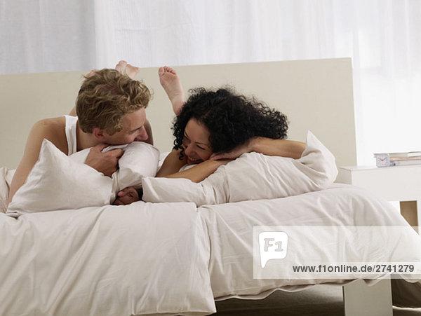 Verspieltes Paar im Bett