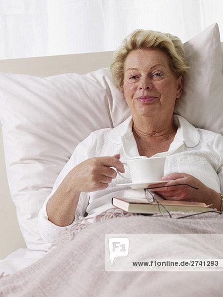 Ältere Dame trinkt Kaffee im Bett