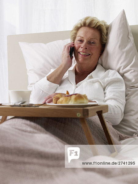 Ältere Dame telefoniert im Bett