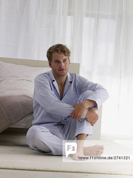 Mann im Schlafanzug sitzt vor dem Bett