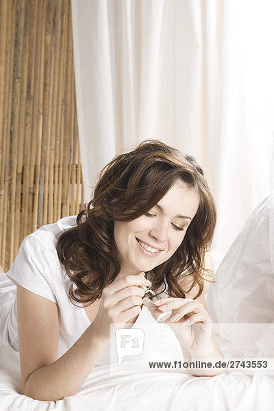 Woman doing manicure in bed