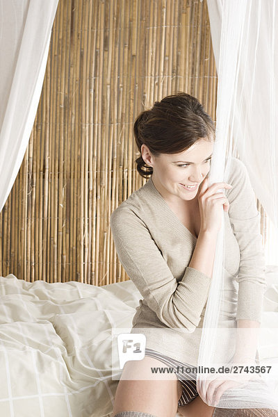 glückliche Frau sitzen auf dem Bett