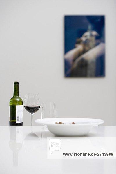 Weinflasche mit einem Glas Rotwein und eine Schüssel auf einem Esstisch