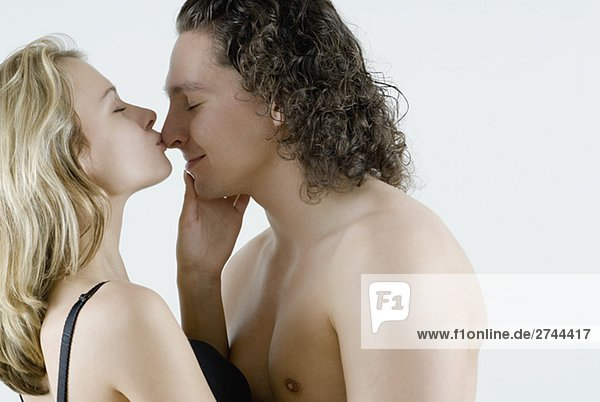Seitenansicht einer jungen Frau einen jungen Mann küssen