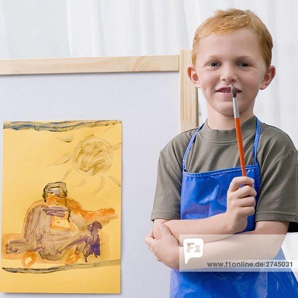 Porträt von Jugendlicher steht vor seiner Malerei in einem Klassenzimmer