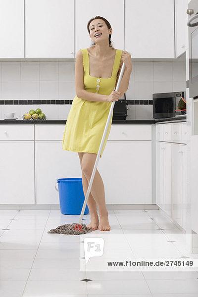 Portrait einer jungen Frau Reinigung den Boden mit einem Mopp