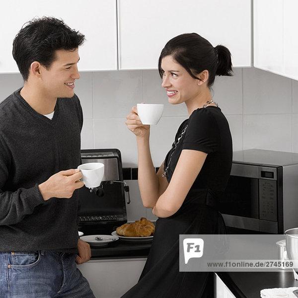 junges Paar hält ihre Kaffeetassen in der Küche und lächelnd