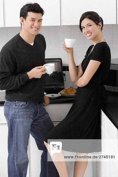 Porträt eines jungen Paares hält ihre Kaffeetassen in der Küche und lächelnd